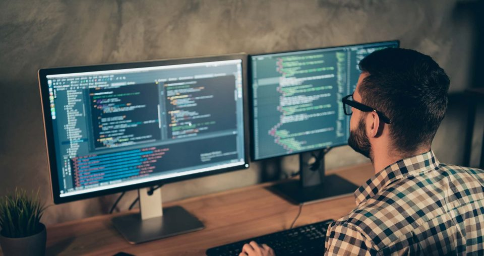 A man with eyeglasses working at a computer