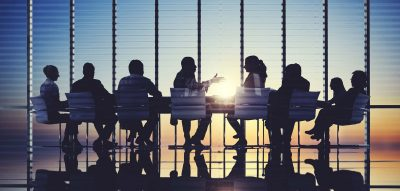 A group of people at a table in a large conference room with the sun coming up in the distance
