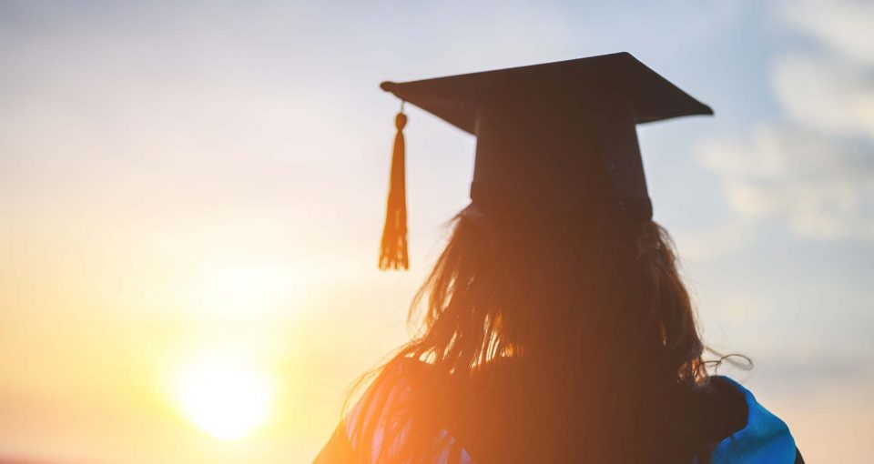 A recent graduate wearing a cap and gown looking at the sun setting on the horizon