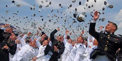 Graduates of the U.S. Naval Academy tossing their hats into the air